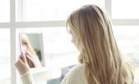 鏡の自分に話しかける女性